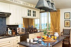 """The writing above this kitchen's cabinetry reads, """"There is nothing, absolutely nothing, half so much worth doing as messing about in boats,"""" from the Wind in the Willows."""