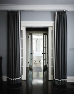View To Principal Bathroom  Place doors to enhance symmetry and flow.  A series of paned doors showcases the principal bathroom like a jewel. The white, grey and charcoal palette is pretty yet polished.  Source: House  Home January 2012 issue  Products:   Drape fabric, Designer Fabrics; ribbon (on drapes), Mokuba; wall colour, Sweatshirt Gray (TH04), Ralph Lauren Home.  Designer: Tommy Smythe