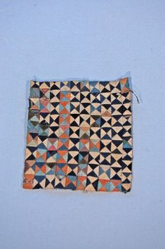 Made by Nanai in Siberia. A cloth for domestic use (?), incomplete; an embroidery-sample. Made from small, triangular pieces of cloth, patched together to form squares (10 x 10). Made from mostly cream and dark blue tabby cotton cloth. One triangle missing; no paper on reverse.