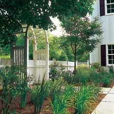 Vertical architectural elements likes arches and arbors tie the landscape to the house and offset a yard's horizontal lines. | Photo: Webb Chappell | thisoldhouse.com