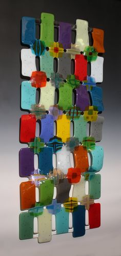 Kaleidoscope by Nina Cambron. An array of fused glass rectangles are richly overlapped with translucent iridescent and patterned medallions reminiscent of the every changing colors & shapes found in a kaleidoscope (see detail). Colors and shapes are projected on the wall behind, creating a stunning 3 dimensional effect. Colors and designs in the kaleidoscope medallions will vary.