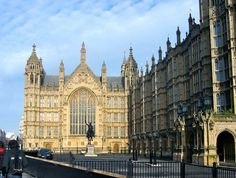 Photo by Mark Yen. View of Old Palace Yard and part of the West Front of the Palace of Westminster (Houses of Parliament) in London. The bronze statue of King Richard I can be seen in front of the South Window of Westminster Hall, and the porte-cochère of Peers' Entrance is to the right. The top of the Clock Tower (Big Ben) can be seen behind the corner turret in the middle.