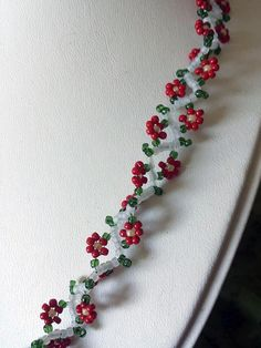 Dress it up or wear it with jeans. Wear it flat or twisted. This versatile daisy chain necklace has been updated for Christmas! Red flowers resemble poinsettias. Created with red, green, pale yellow, and white Japanese seed beads on super-strong Fireline.    Closes with a brass colored nickel-free magnetic clasp for ease of wear.