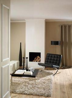 Sfeer woonkamer. Hoogpolig vloerkleed, designstoeltje, haard..
