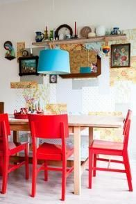 cute and colorful. red chairs, blue lamp, and oh so homey wall.