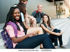 Young woman smiling with friends in the background on stairs