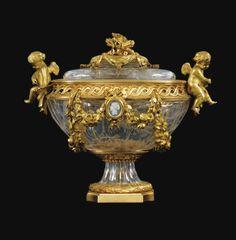 Urne couverte en cristal de roche et bronze doré de style Louis XVI dans le goût de Pierre Gouthière, d'époque Restauration, vers 1820-1830. Cristal de roche gravé, la prise du couvercle à décor de roses et carquois, les anses ornées de chérubins, la panse ceinte d'une frise d'entrelacs ajourée, ornée de chaque côté d'une guirlande de roses et d'un camée, reposant sur un piédouche terminé par un tor de laurier