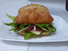 Our dishes using heirloom tomatoes and produce: this is A Ciabatta Sandwich: made with our Heirloom Tomato (Japanese Trifele) and our Heirloom Lettuce (Reine de Glase) with Havarti Cheese, Rosemary Ham, Onion, Mayo and seasoned with cracked Pepper. Havarti Cheese, Cracked Pepper, Heirloom Tomatoes, Ciabatta, Lettuce, Ham, Onion, Sandwiches, Dishes
