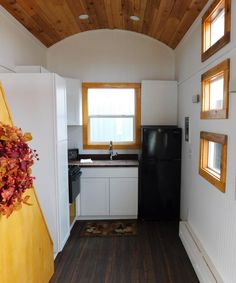 The kitchen features white Arcadia cabinets, butcher block countertops, an apartment style refrigerator, a stainless steel undermount sink, and a tall pantry cabinet.