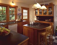 Original bungalow kitchens were often basic and modest. Subsequent remodeling and renovation has created kitchens that accommodate today's lifestyles. Craftsman details, stained wood trim and cabinetry with the look and feel of furniture maintains the vintage quality of this home.