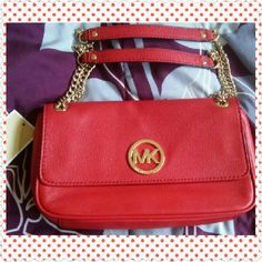 """NWT Rare Michael Kors Fulton Gorgeous bright cherry red genuine leather authentic Michael Kors fulton flap shoulder bag. Rare hard to find color. Magnetic front closure. Magnetic exterior rear slip pocket closure. Interior has 6 card slots, one slip pocket and a deep zip pocket.  Straps can be worn short with 10"""" drop or longer with about 18"""" drop. Could also be used as clutch. Beautiful any way carried. Is 10"""" long, 6"""" high, has a 2.25"""" depth. Stunning gold tone hardware. Open to reasonable…"""