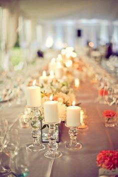 A reception table filled with pillar candles - varying heights - creates a soft backdrop for a wedding reception. Reception Decorations, Wedding Centerpieces, Wedding Table, Wedding Reception, Our Wedding, Reception Table, Centrepieces, Wedding Favors, Wedding Invitations