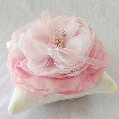 Prachtige handgemaakte hoofdkussen in mat ivoor satijn beschikt over een enkele oversized bloem in tinten van roze. Bloem is verkregen uit zorgvuldig kaars-zingen lagen van satijn en chiffon. Een trio blush roze parels accenten het center naast roze satijn en organza lint banden. Een