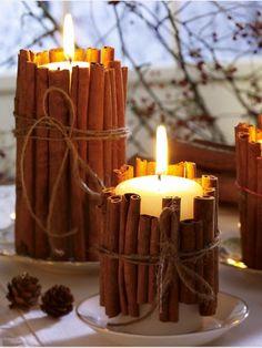 Δένουμε ξυλάκια κανέλας γύρω από κεριά. Τα ξυλάκια ζεσταίνονται και το σπίτι γεμίζει με την υπέροχη μυρωδιά τους.
