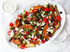 This recipe for loaded Greek fries is made with seasoned potato wedges topped with a cucumber and tomato salad, feta and a creamy garlic-scallion sauce! #rachaelhartleynutrition #thejoyofeating #frenchfries #appetizerrecipes #appetizer #vegetarian #vegetarianrecipes #potatorecipes #greekrecipes #mediterraneandiet