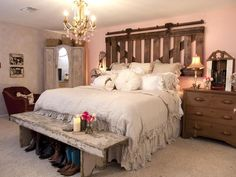 Cowgirl Flair! An old barn gate and barn-door hardware are repurposed into a rustic headboard. A crystal chandelier, antique furniture and a few other dainty touches counteract the roughness with a bit of girly style.