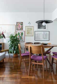 Sala de jantar tem mesa redonda e cadeiras com estofado roxo.