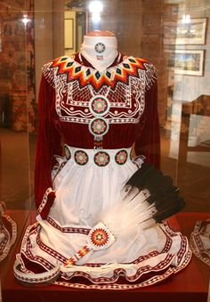 Traditional Mississippi Choctaw dress; the fan is more likely inspired by pan-indianism/powwows.