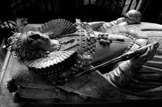 """The effigy depicts Queen Elizabeth 1 in her last years of reign holding the orb and scepter.  Her  half sister Queen Mary, other daughter of Henry the VIII of the Tudors lays beside her in Westminster Abbey.  On the base of the tomb it reads """"Partners both in throne and grave, here rest we two sisters, Elizabeth and Mary, in the hope of resurrection""""."""