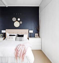 Dark feature wall behind a white bed.