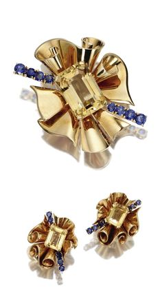 18 KARAT GOLD, CITRINE QUARTZ AND SAPPHIRE BROOCH AND EARCLIPS, TRABERT & HOEFFER, MAUBOUSSIN, REFLECTION, CIRCA 1940.  Each centering an emerald-cut citrine bisected diagonally by a ray of round sapphires, within a ruffled frame of gold drapery, brooch signed Trabert & Hoeffer, Mauboussin and Reflection.