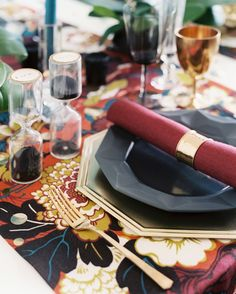 A pop art table runner in an outsized floral pattern is the perfect backdrop for bold geometric dinnerware and accents of gold.