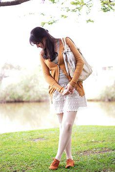 Look romântico com peças em tons neutros saia de renda regata cardigã mostrada meia calça e oxford