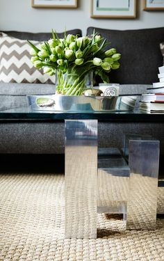A Stylish West Village Home for an American Fashion Force: A lush arrangement of tulips sits atop the living room's most eye-catching conversation piece: a 20th-century Brutalist coffee table from Elizabeth Bauer Design.