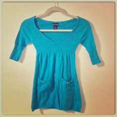 V-Neck Bright Teal/Tuorquoise Babydoll Top. V-neck. Ribbed mid-sleeves, adorable front pockets with button detail. 100% cotton. Sweaters