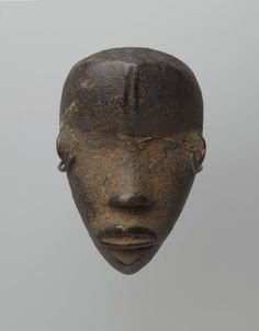 Brooklyn Museum: Arts of Africa: Personal Miniature Mask (Ma Go)   -    function as amulets among the Dan and neighboring cultures, linking the owner with a particular spirit force that provides assistance and protection. Normally, they are kept hidden and brought out only during special rituals.    Wood, organic matter   Liberia   19th or 20th century  4 3/4 x 3 x 2in. (12.1 x 7.6 x 5.1cm)
