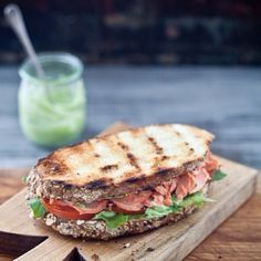 Grilled salmon sandwich, with tomatoes, pesto & salad on toasted whole wheat bread :)