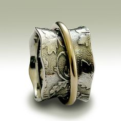 Nothing else matters ~~~~~~~~~~~ This beautiful band is unisex and makes a wonderful wedding band. The main band is made of oxidized sterling silver with filigree, leaf design. Surrounding the band, a beautiful gold filled spinner.(R1736A). © 2011 Artisanimpact Inc. All rights reserved. Construction & Dimensions: ~~~~~~~~~~~~~~~~~~~~~~~~~~ Sterling silver, gold filled. Approximate width: 11mm -13mm (wavy) We can make any size, including quarter sizes. For this wider band, we suggest ad...
