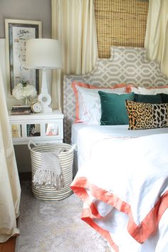 upholstered headboard, coral trimmed shams, leopard print pillow