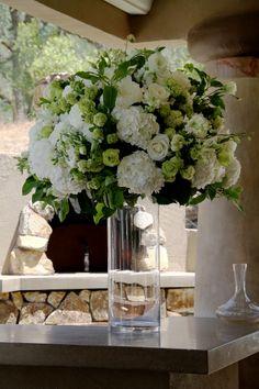 White  Green Ceremony flowers on glass cylinder transferred to the Bar. White Hydrangea, peonies, snowball viburnum, roses. www.fleursfrance.com Fleurs de France