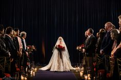 Bride with a red bouquet and full length veil makes a dramatic entrance to her ballroom winter ceremony lit by lots of candles lining the aisle   Flora Nova Design Seattle Ballroom Wedding Reception, Wedding Reception Flowers, Wedding Ceremony Decorations, Wedding Flower Arrangements, Floral Centerpieces, Floral Wedding, Winter Wedding Ceremonies, Seattle Wedding, Event Design