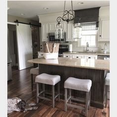 Modern farmhouse style kitchen with sliding barn door /pantry.   White cabinets make the space seem bigger and tie in the white trim throughout the ranch home.