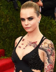 Cara Delevingne had a temporarily Chinese floral style body Tattoo at the Met Gala 2015.