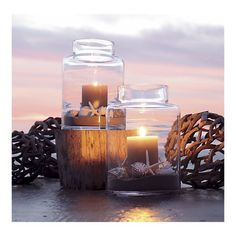 Elegant hurricanes filled with sand, shells and glowing candles offset by driftwood orbs...magical!