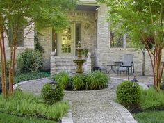 Looks very French with the fountain, pea gravel, boxwood and gray tones.
