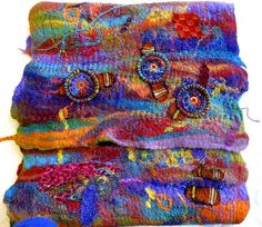 Ro Bruhn:  Felt that she made.  She added fabric, then stitched and decorated.  See detail pic
