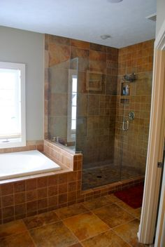 Beautiful built-in large soaking bathtub next to custom made walk-in glass shower.