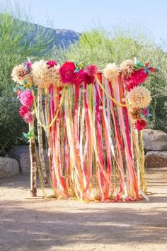 Bright coloured DIY wedding backdrop with ribbons and pom poms