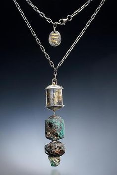 Large hollow formed oval bead hangs from a beveled chain along with Leland blue stone nuggets and a small emerald nugget.