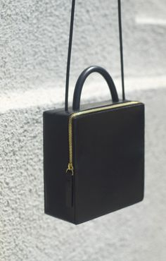 Shit. I keep seeing this bag. I really like the shape. Size can be accepted. BUT Perceived Value not a match!!!   18 × 18 × 7 cm $450.00 Smooth Black Italian Leather, Solid Rubber Handle, Rubber shoulder strap, Zip Closure Building Block