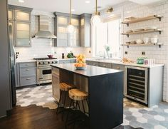 Traditional kitchen with a twist, featuring mixed tile and hardwood floors, white subway tiles, gray cabinets and open shelving for storage | SuzAnn Kletzien Design