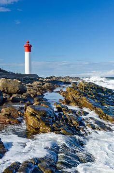 Umhlanga Rocks lighthouse watches over the rocky coastline just north of Durban in KwaZulu Natal - South Africa