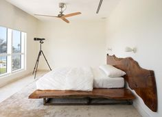 Live-edge tree slabs are used to form both the bed's platform and headboard, adding an organic note to this Miami Beach townhouse bedroom by Magdalena Keck Interior Design. Photo by Jeff Cate.
