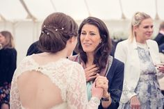 wedding guests talks with bride at The Priory Wareham wedding. Photography by one thousand words wedding photographers