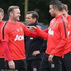 Partners: Wayne Rooney and Robin van Persie share a joke during a training session...
