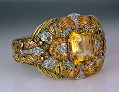 Exceptional Art Nouveau Bangle Bracelet C1910. A unique Art Nouveau bangle bracelet of an openwork floral design, centered with a prong-set emerald cut citrine framed by superbly chased orange-yellow and green 18K gold foliage with diamond-set platinum highlights. Circa 1910 | JV